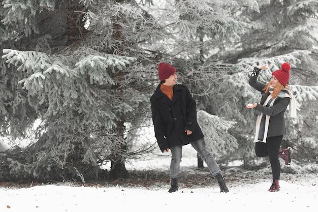 Lindo casal brincando com neve tiro longo