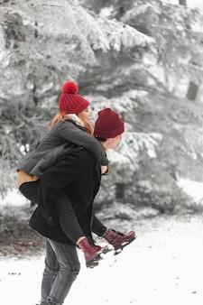 Lindo casal brincando na neve lateralmente