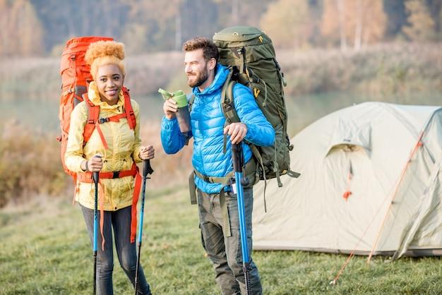 Lindo casal caminhando com mochilas coloridas no gramado com a barraca ao fundo, homem bebendo água da garrafa