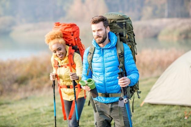 Lindo casal caminhando com mochilas coloridas no gramado com uma barraca ao fundo