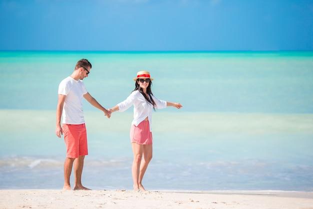 Lindo casal caminhando na praia e curtindo as férias de verão