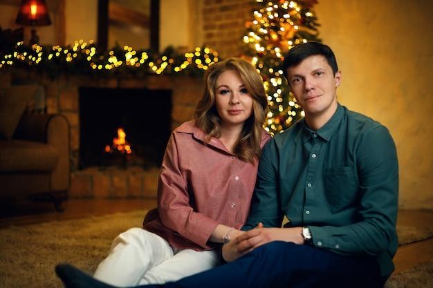 Lindo casal caucasiano de meia idade posando no interior do ano novo com uma árvore de natal e guirlandas