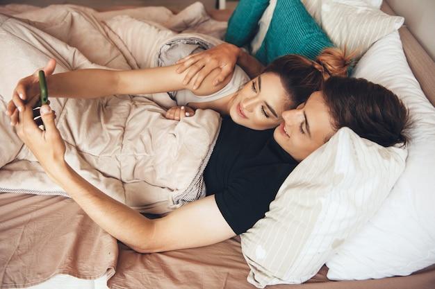 Lindo casal caucasiano deitado na cama sorrindo enquanto faz uma selfie usando um telefone celular