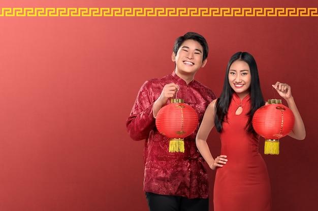 Lindo casal chinês segurando lanternas vermelhas em fundo vermelho