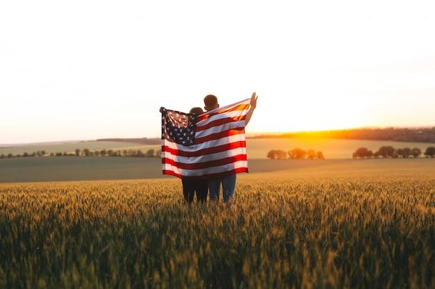 Lindo casal com a bandeira americana em um campo de trigo ao pôr do sol. dia da independência, 4 de julho.