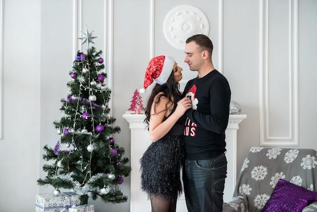 Lindo casal com árvore de natal posando no estúdio
