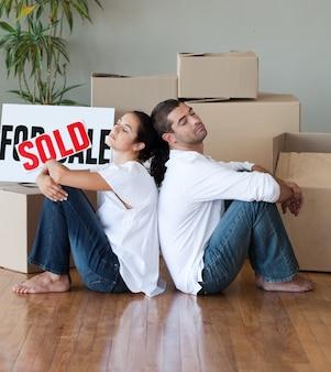 Lindo casal com caixas de desembalagem se mudando para uma nova casa
