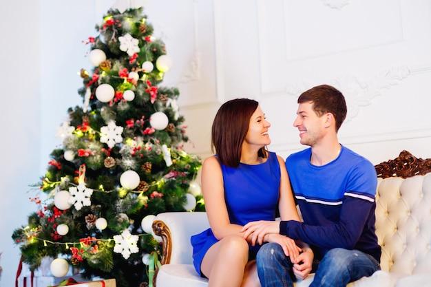 Lindo casal com roupas azuis, sentado no sofá perto da árvore de natal, em um lindo quarto branco decorado