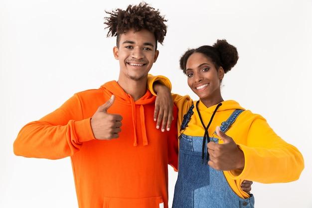 Lindo casal com roupas coloridas aparecendo com os polegares para cima, isolado sobre uma parede branca