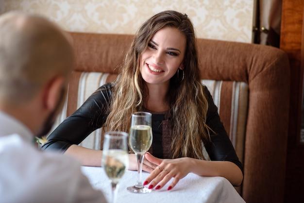 Lindo casal comemorando e bebendo champanhe no restaurante