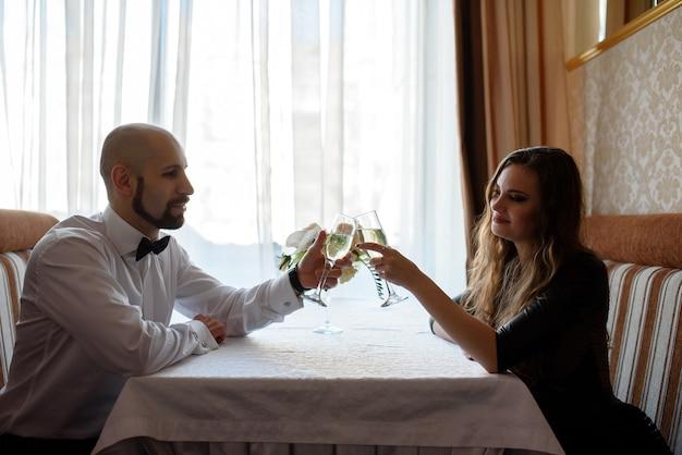 Lindo casal comemorando e bebendo champanhe no restaurante.