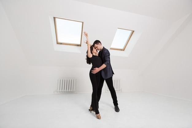 Lindo casal dançando bachata na parede branca