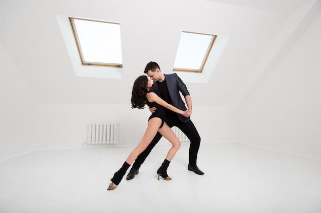 Lindo casal dançando bachata no fundo branco no estúdio