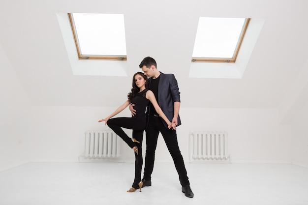 Lindo casal dançando no fundo branco no estúdio