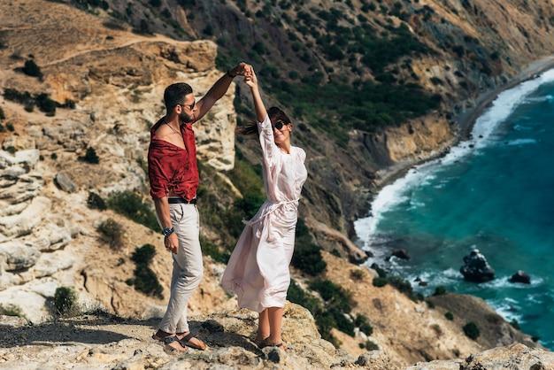 Lindo casal dançando uma valsa à beira-mar. casal feliz de férias. amantes da lua de mel. homem e mulher à beira-mar. um casal apaixonado se diverte no mar. copie o espaço