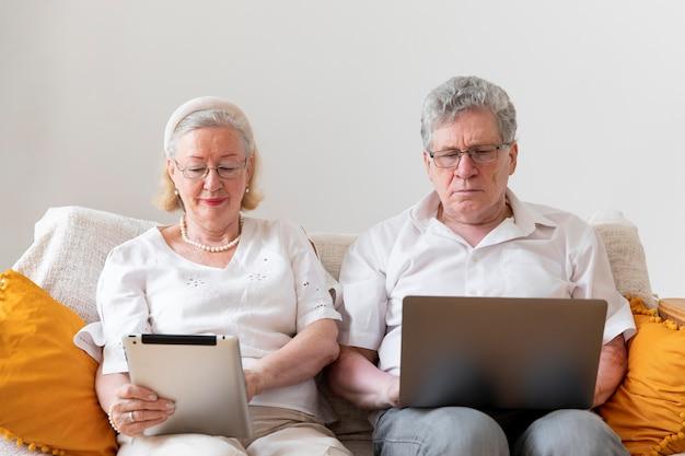 Lindo casal de avós aprendendo a usar um dispositivo digital