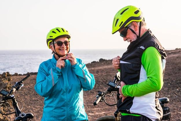 Lindo casal de dois idosos andando de bicicleta juntos na praia rochosa - conceito de estilo de vida ativo e fitness - mulher madura olhando sorrindo para o marido
