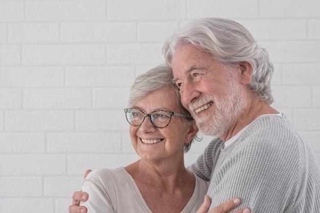 Lindo casal de dois idosos felizes se abraçando - em pé sorrindo em casa - conceito de aposentadoria serena