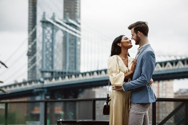 Lindo casal de homem americano com barba e concurso mulher oriental abraçar um ao outro