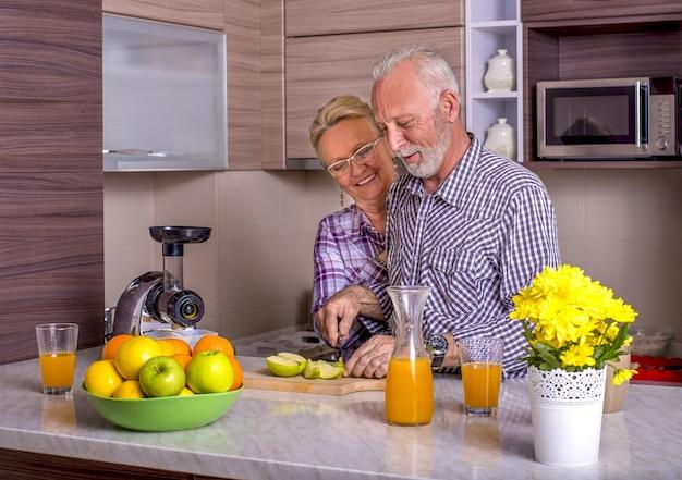 Lindo casal de idosos cozinhando um com o outro na cozinha