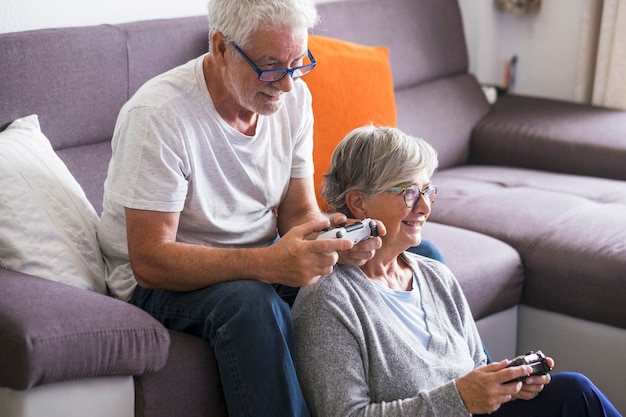 Lindo casal de idosos e maduros casados, andando de bicicleta doble, tandem, juntos para se divertir em um ótimo e ensolarado dia - mulher sentada no chão e homem sentado no sofá