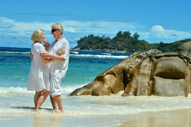 Lindo casal de idosos em pé na praia se abraçando