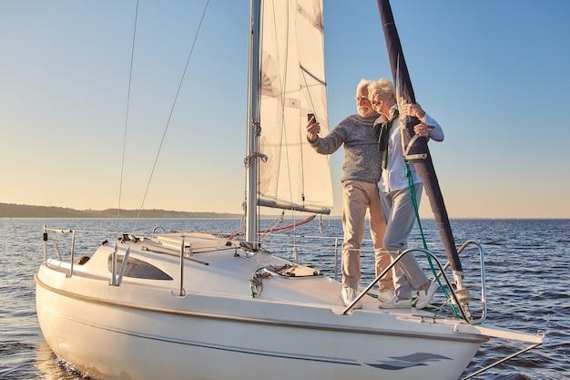 Lindo casal de idosos fazendo selfie no smartphone em pé ao lado de um veleiro ou iate