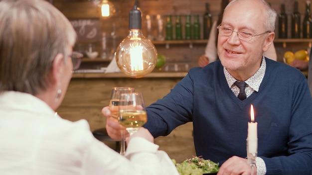 Lindo casal de idosos fazendo torradas e tilintando de copos. comer no restaurante. homem e mulher na casa dos sessenta.