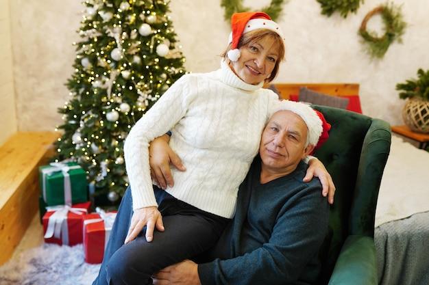 Lindo casal de idosos feliz comemorando o ano novo em casa, árvore de natal decorada