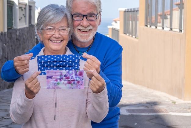 Lindo casal de idosos já vacinado contra a infecção por coronavírus - sorri feliz ao ar livre tirando suas máscaras protetoras