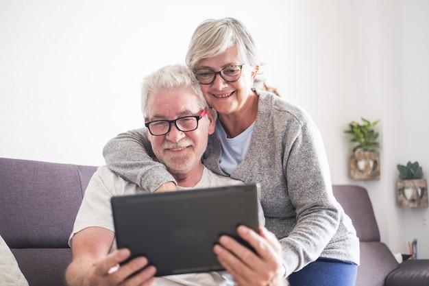 Lindo casal de idosos ou pessoas maduras em casa se abraçaram olhando para o mesmo tablet ou laptop - aposentados com óculos usando a nova tecnologia