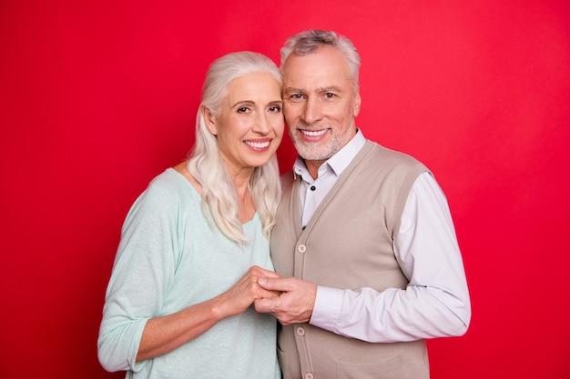Lindo casal de idosos posando contra a parede vermelha