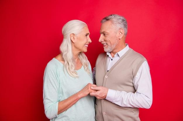Lindo casal de idosos posando junto contra a parede vermelha