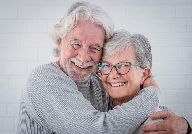 Lindo casal de idosos se abraçando com amor, em casa olhando para a câmera