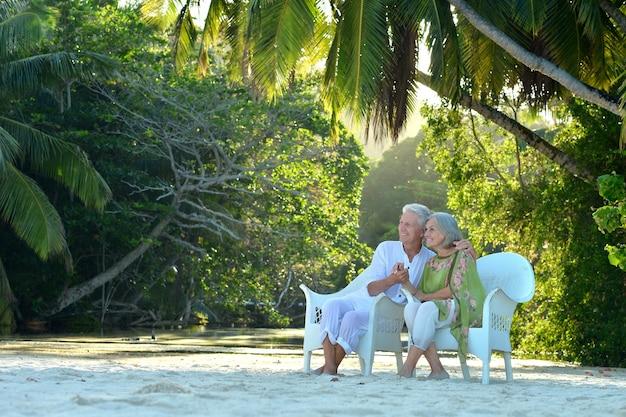 Lindo casal de idosos sentado em um fundo de palmeiras