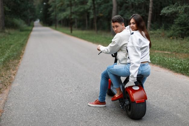 Lindo casal de jovens em jeans e suéteres brancos em uma bicicleta eletrônica
