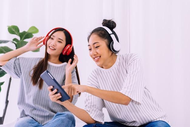 Lindo casal de lésbicas asiáticas ouvindo música juntos em casa, conceito lgbt