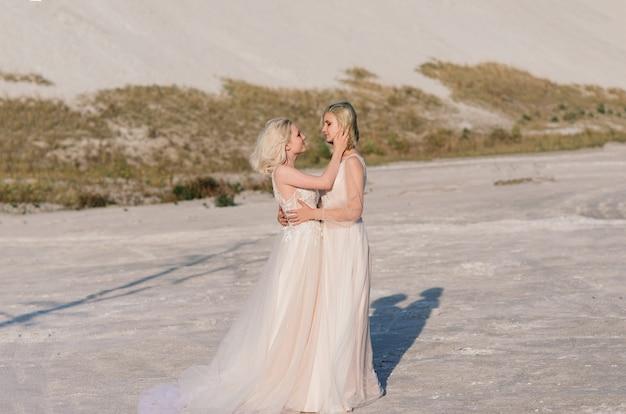 Lindo casal de lésbicas caminhando na areia à beira de um rio no dia do casamento