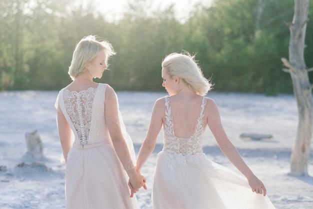 Lindo casal de lésbicas caminhando na areia ao longo da margem de um rio no dia do casamento