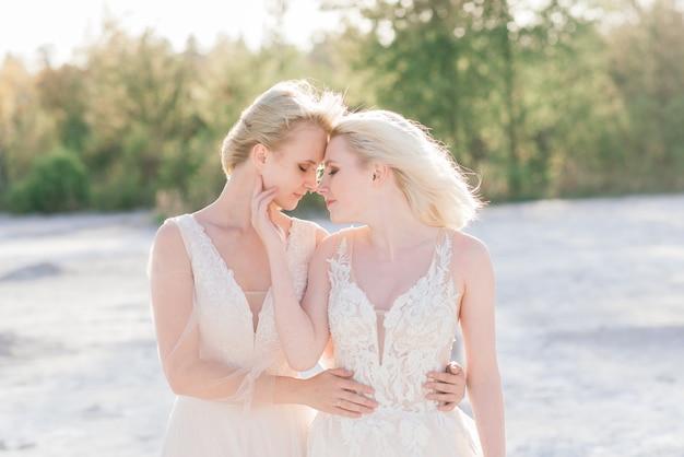 Lindo casal de lésbicas caminhando na areia ao longo da margem do rio no dia do casamento