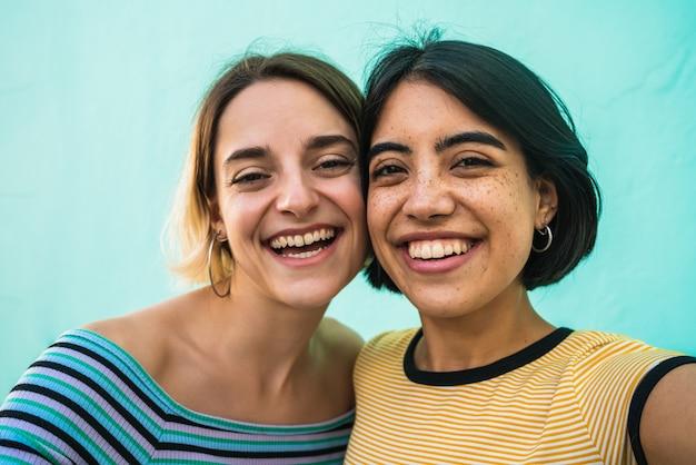 Lindo casal de lésbicas tirando uma selfie.