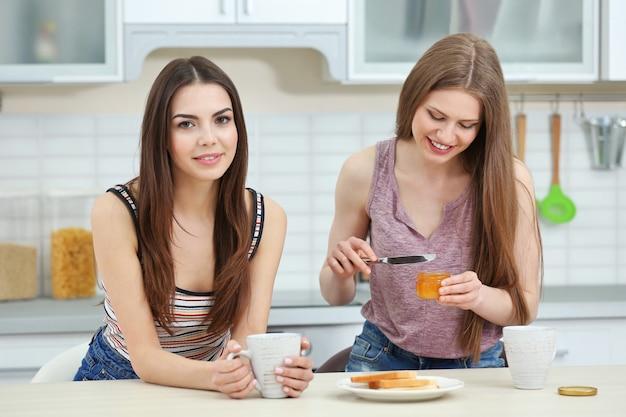 Lindo casal de lésbicas tomando café da manhã em uma cozinha iluminada