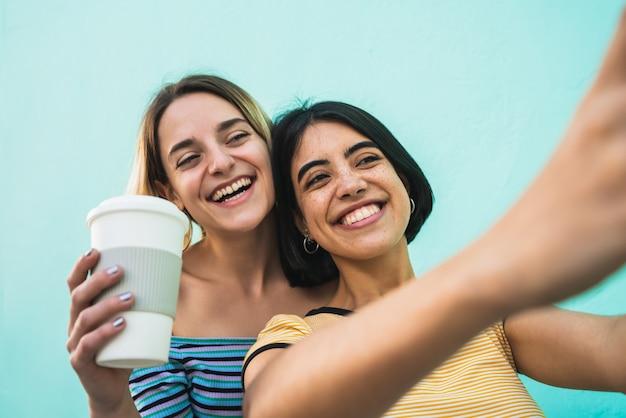 Lindo casal de lésbicas tomando uma selfie com telefone.