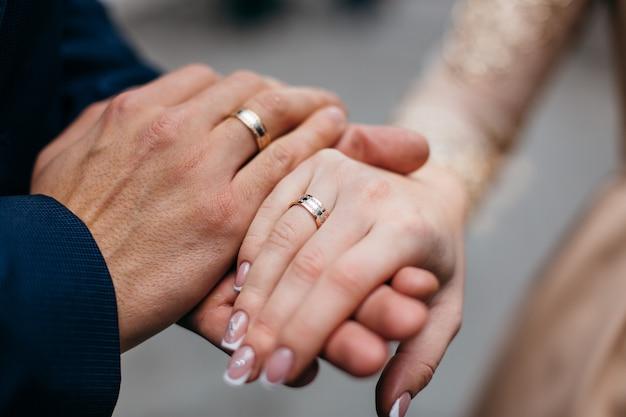 Lindo casal de mãos com anéis de casamento