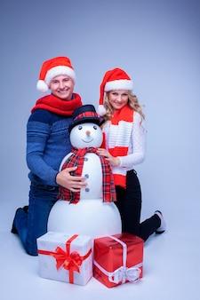 Lindo casal de natal com chapéu de papai noel sentado com presentes e boneco de neve em fundo azul