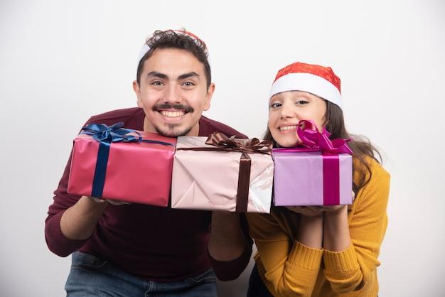 Lindo casal de natal segurando presentes em um fundo branco.