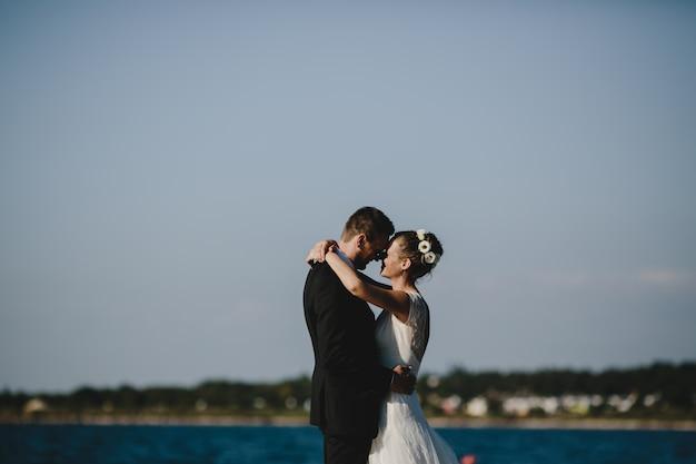 Lindo casal de noivos abraça outro pé concurso na margem do lago