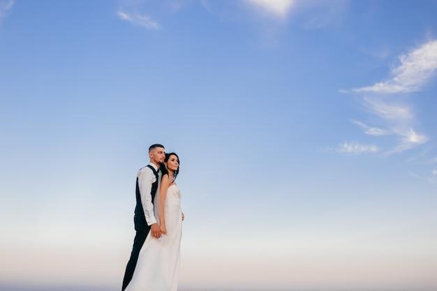 Lindo casal de noivos abraçando ao ar livre.