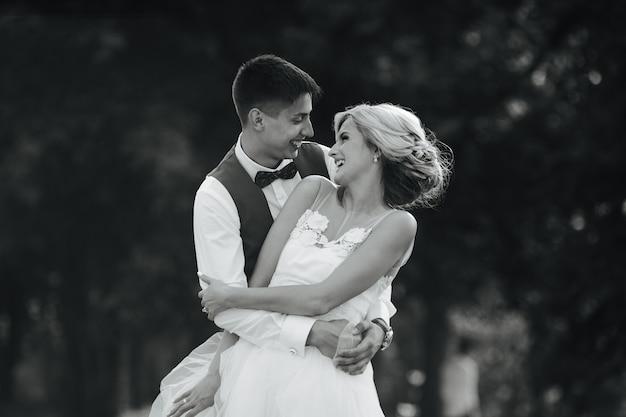 Lindo casal de noivos abraçando no parque