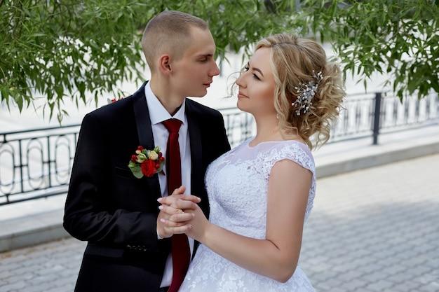 Lindo casal de noivos amorosos registra um casamento e caminha ao longo do belo calçadão. felicidade e amor aos olhos de homens e mulheres. rússia, sverdlovsk, 15 de junho de 2019